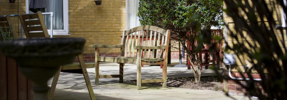 A bench in the back garden at Rowanweald Nursing Home.
