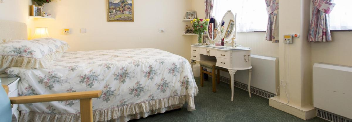 A pretty floral bedroom at Pinewood Residential Care Home.
