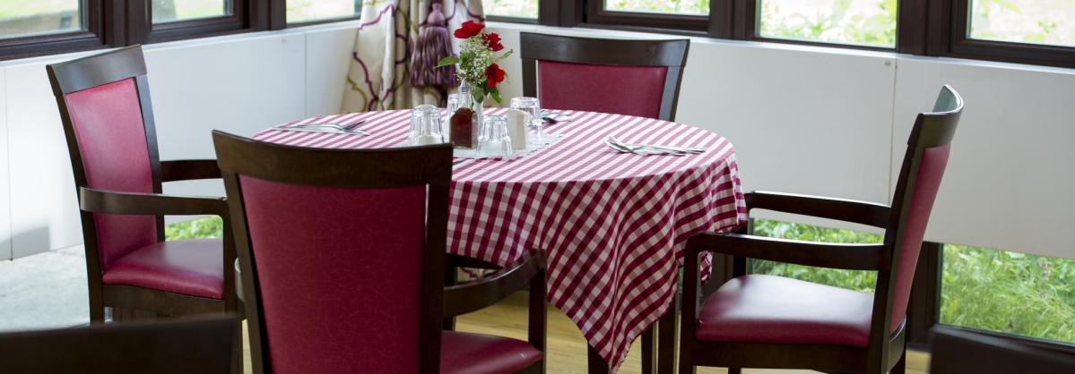 The dining room at Pinewood Residential Care Home with chequered table cloth and flowers.