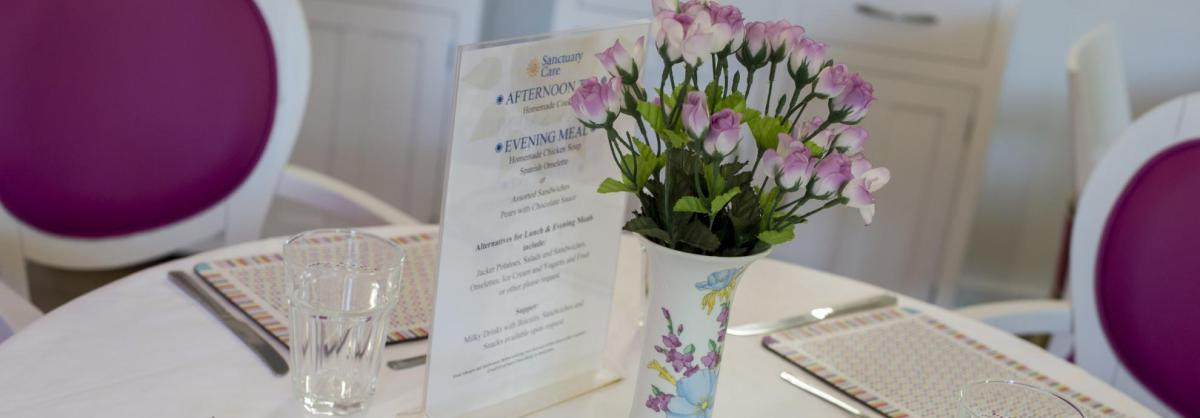 A dining table at the Parkview House Residential Care Home with simple place settings, tumblers and flowers in a vase.