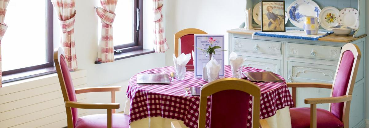 The country style dining room at Lyons Court Residential Care Home has chequered table cloths and a blue dresser.