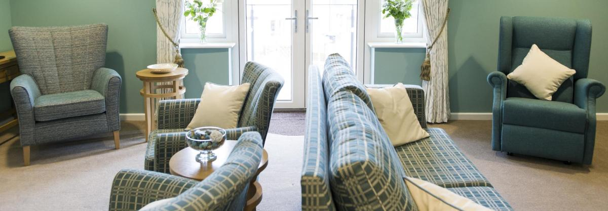 The cosy lounge at the Juniper House Residential Care Home has wing-backed chairs and soft lighting.