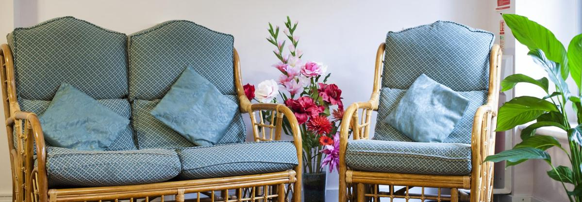 Wicker chairs with soft cushions in one of the seating areas atAashna House.