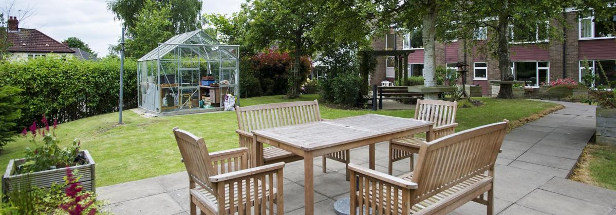 Wooden table and chairs in the courtyard garden at Bradwell Court Residential Care Home.