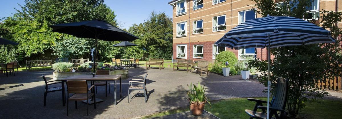 The courtyard garden with tables and umbrellas at Breme Residential Care Home.