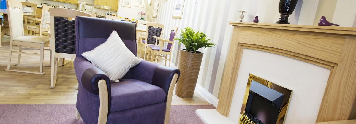 A cosy lounge chair next to an open fire at Haven Residential Care Home.