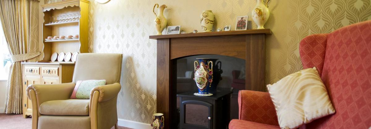 A comfortable lounge with an open fire at Heathlands Residential Care Home