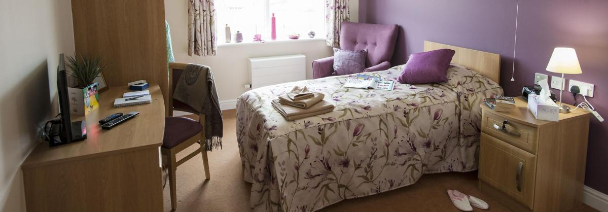 A stylish bedroom at Lime Tree Court Residential Care Home with coordinating purple accessories.