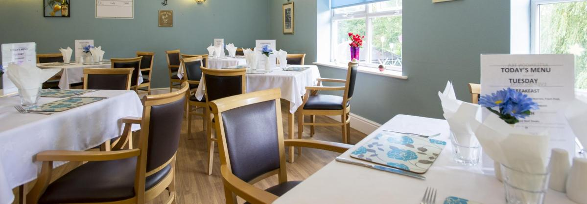 The softly lit dining room at East Park Court Residential Care Home with tables set for service.