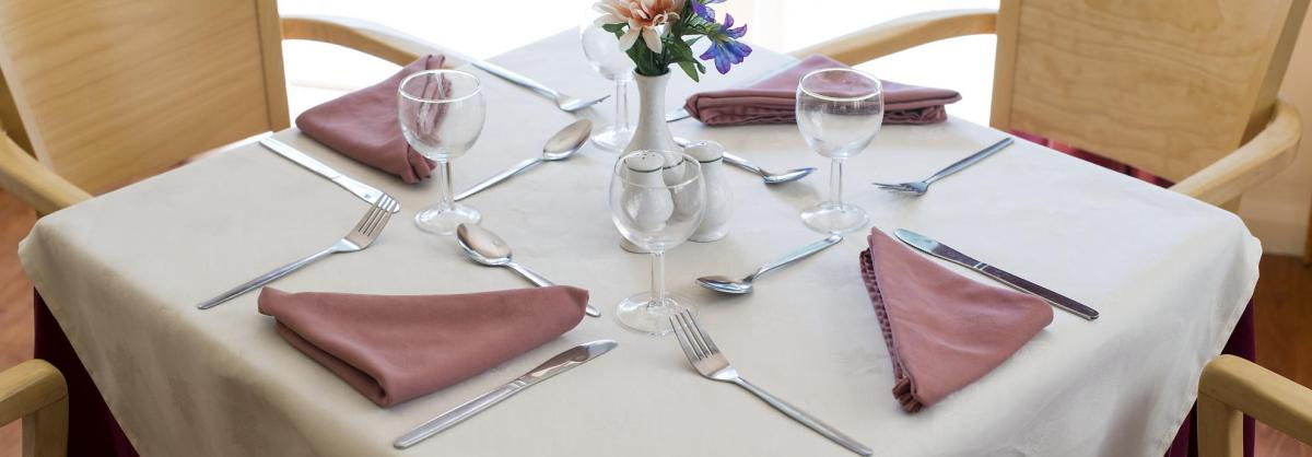 A dining room table, set with napkins and wine glasses at Fernihurst Care Home.