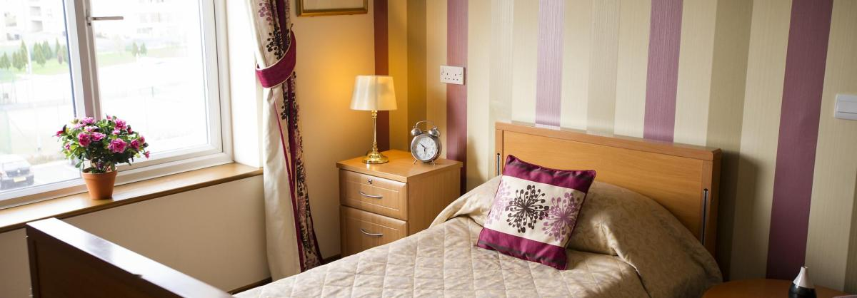 A wooden bed with head and footer boards in a stripy bedroom at Hatfield Residential and Nursing Home.