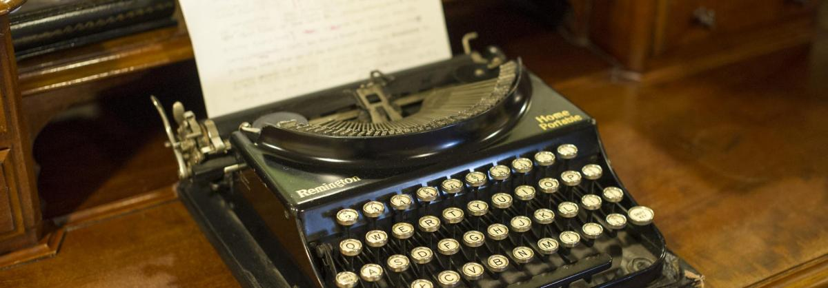 A beautiful black and gold typewriter on a bureau in a reminiscence station.