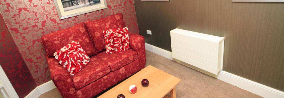 A stylish red sofa in the lounge at Highcroft Hall Residential Care Home.