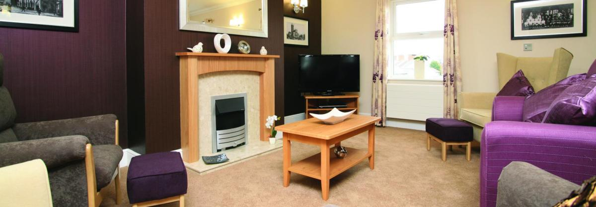 The fireplace and feature wall in the Highcroft Hall Residential Care Home.