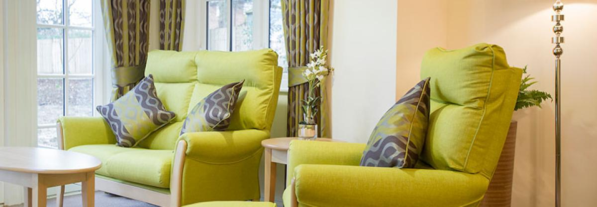 The stylish lounge at Iffley Residential and Nursing Home has relaxing chairs, TV and real fire.