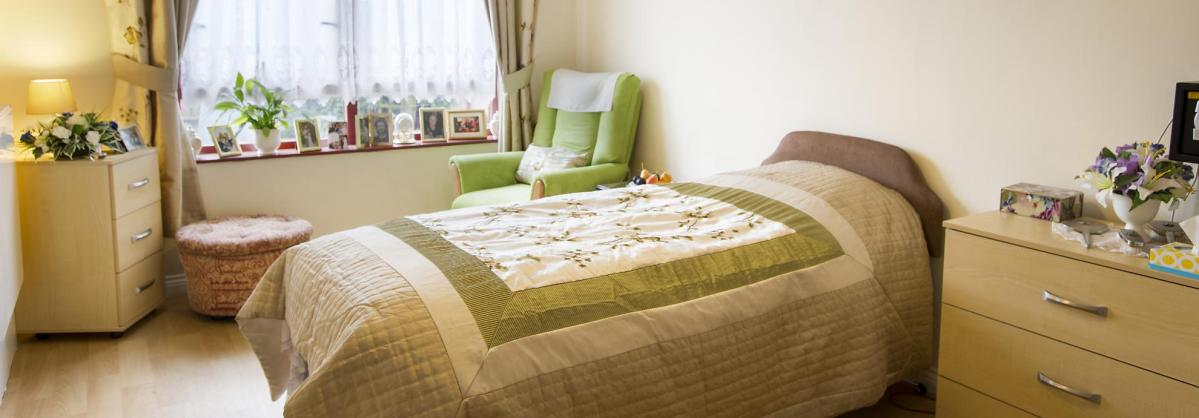 A bedroom in Lammas House Residential Care Home with wooden floors and pretty soft furnishings.