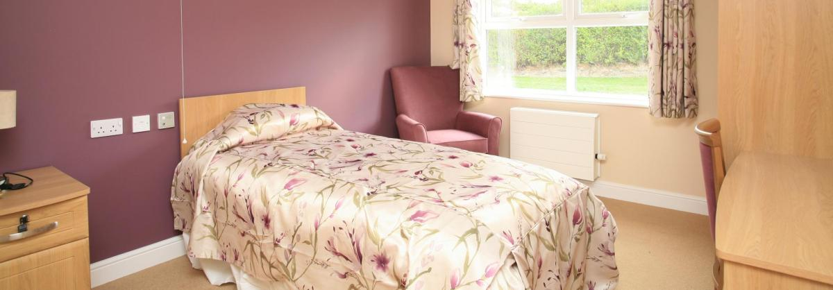 A dusty pink bedroom at Park View Residential Care Home with wooden furniture.
