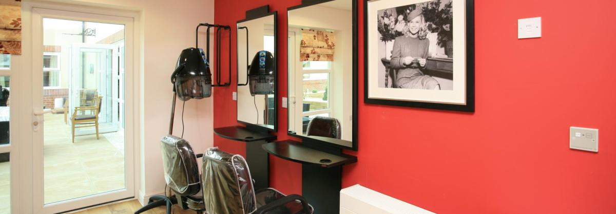 The contemporary hair dressing salon at Park View Residential Care Home has stylish red and black fittings.