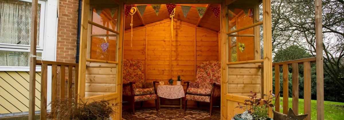 The summer house at Westmead Care Home with bunting and comfy seats.