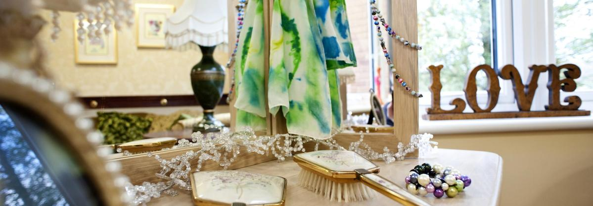 A dressing table with three mirrors, hair brushes jewellery and scarfs.