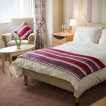 A bedroom with table and chairs by the window at Haven Residential Care Home.