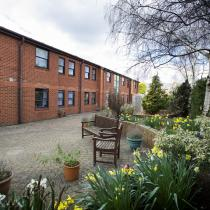 Comfortable benches, flower pots and raised lawn in the back garden at the Greenslades Care Home.