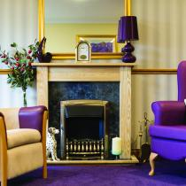 A striking purple and grey lounge with open fire at Hatfield Residential and Nursing Home.