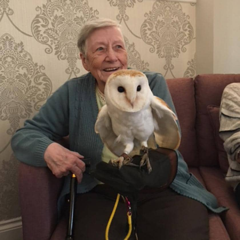 Resident Pat holding an owl at Beach Lawns