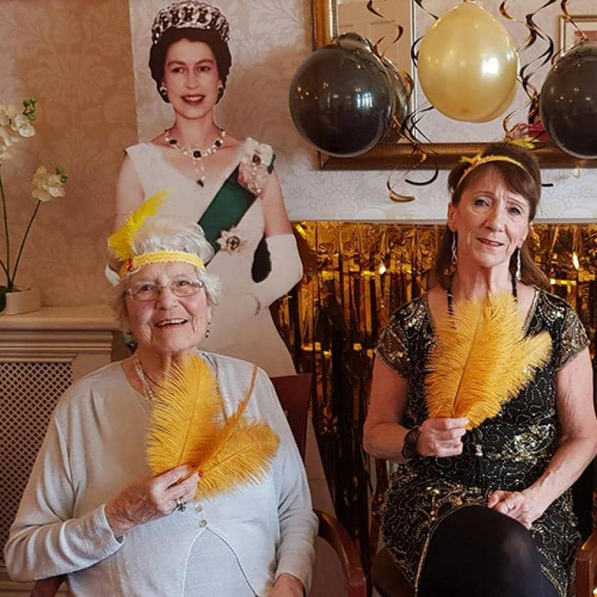 Resident and care assistant celebrating the queen