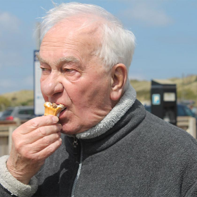 Sanctuary Care resident Ken Andrews eating an ice cream at the beach
