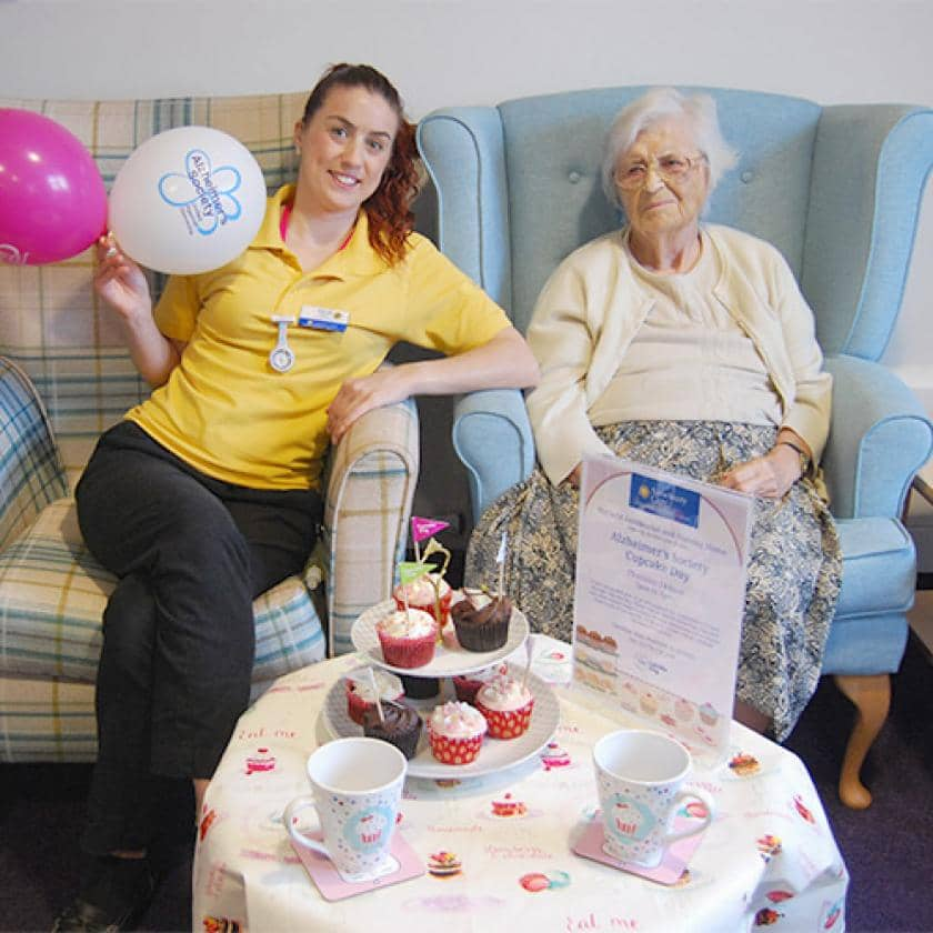 Activities leader and resident enjoying tea and cake