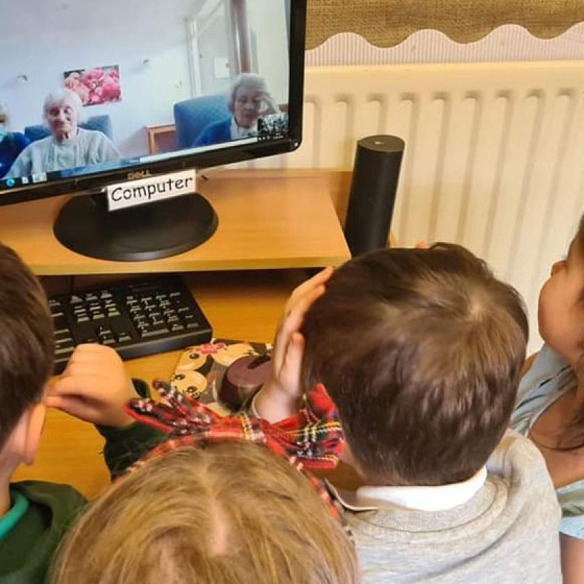 Children gather around a computer to have a zoom call with two residents from Mull Hall Care Home