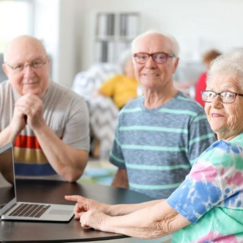 Three seniors socialise together while viewing a laptop