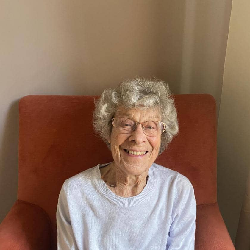 Jean, resident at Juniper House Care Home in Worcester, sits in a chair and smiles.
