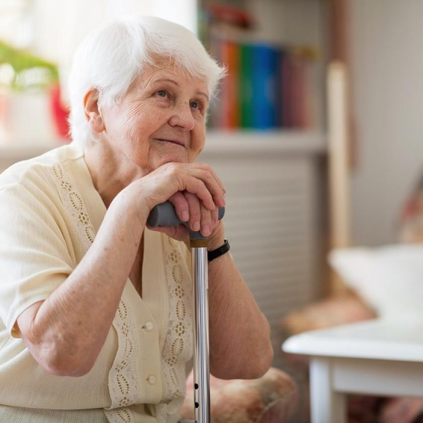 An elderly lady sits on a chair while  leaning on her walking stick
