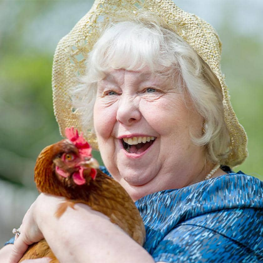 Sanctuary care resident Moe Goust holding a chicken