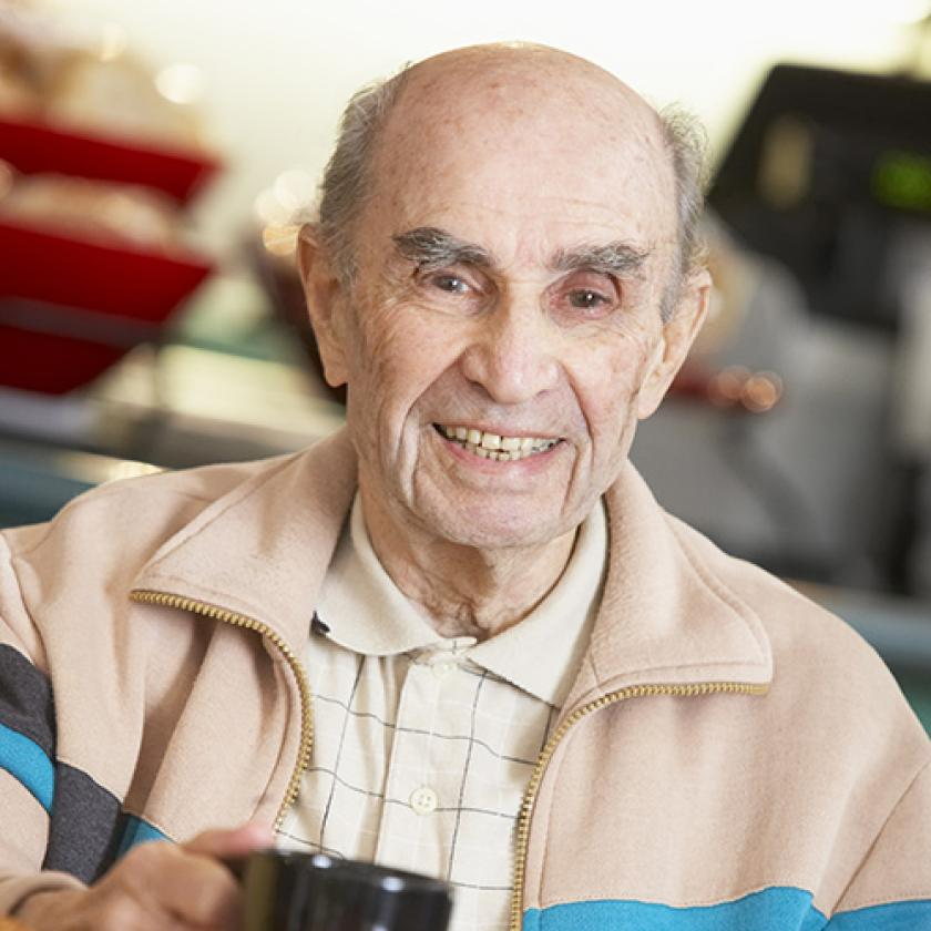 Senior man smiling as he drinks a cup of coffee
