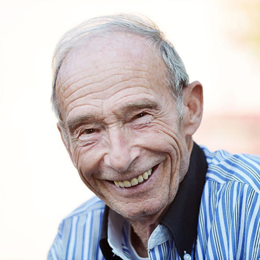 Elderly man wearing a striped shirt smiles as he has his photo taken