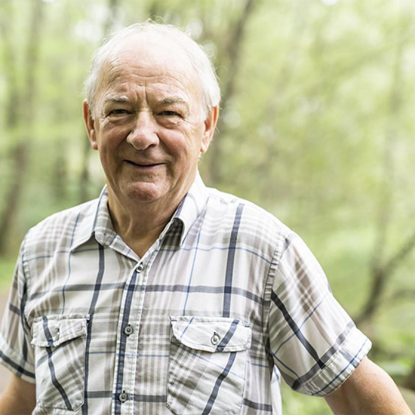 Stock image of a senior gentleman standing in a forrest
