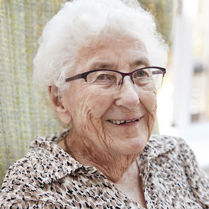 Elderly woman sitting in a chair smiling