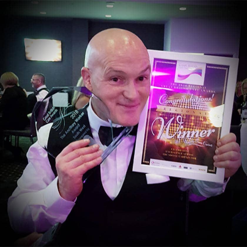 Staff member posing with awards